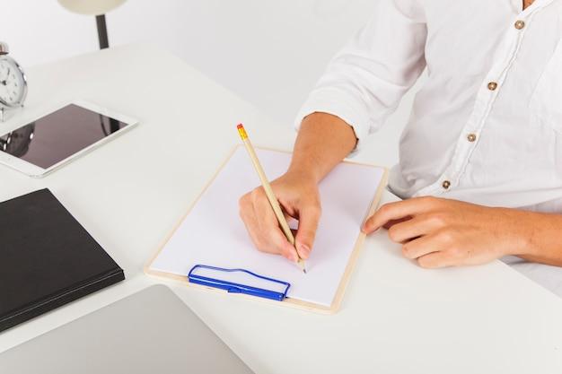 Handen schrijven op klembord