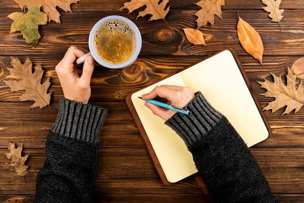 Handen schrijven op notebook bovenaanzicht