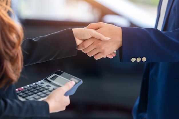 [handen schudden in autoshow] autobedrijf, autoverkoop, deal, gebaar en mensenconcept, koop nieuwe auto's die verkoopovereenkomsten sluiten met autodealers bij autodealers.