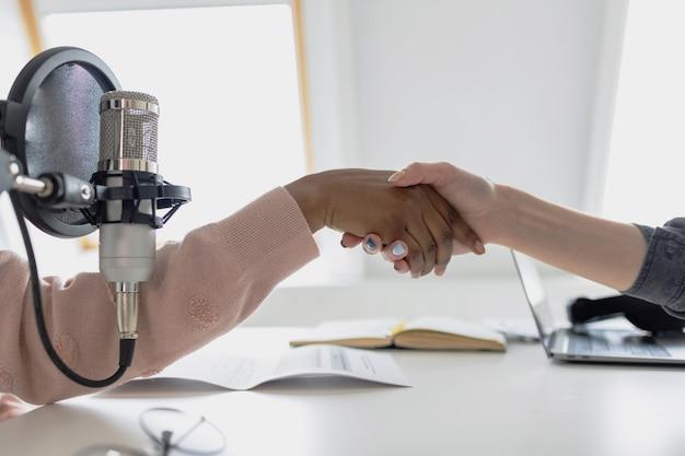 Handen schudden met twee mensen die een podcast of audio-inhoud opnemen een handdruk van een afrikaan