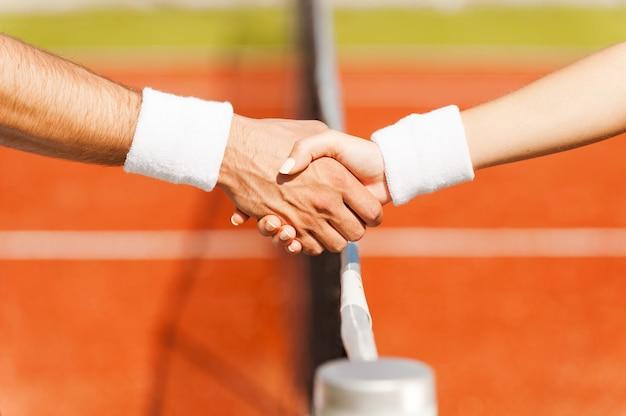 Handen schudden na goed spel. close-up van man en vrouw in polsband die handen schudden op het tennisnet