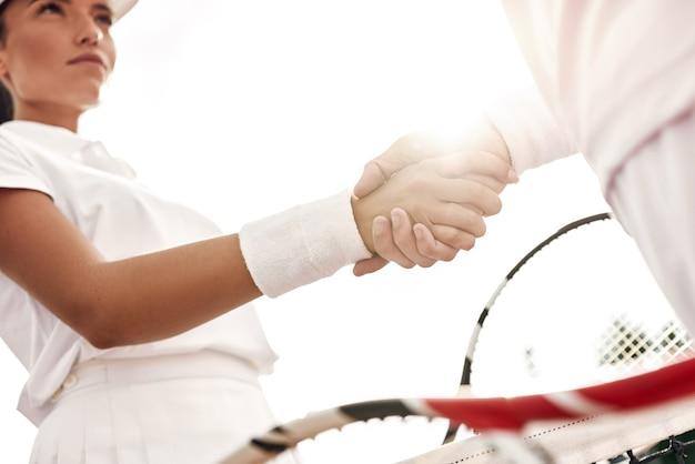 Handen schudden na goed spel close-up van man en vrouw in polsband die handen schudden