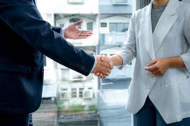 Handen schudden na teamvergadering van zakenvrouw en zakenlieden om strategieën te plannen om het bedrijfsinkomen te verhogen. heb een brainstormgrafiekanalyse en bespreek het succes van het nieuwe doelwit.