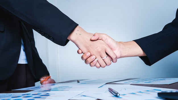 Handen schudden op de bijeenkomst van het succesconcept van het zakelijke vrouwenteamwerk.