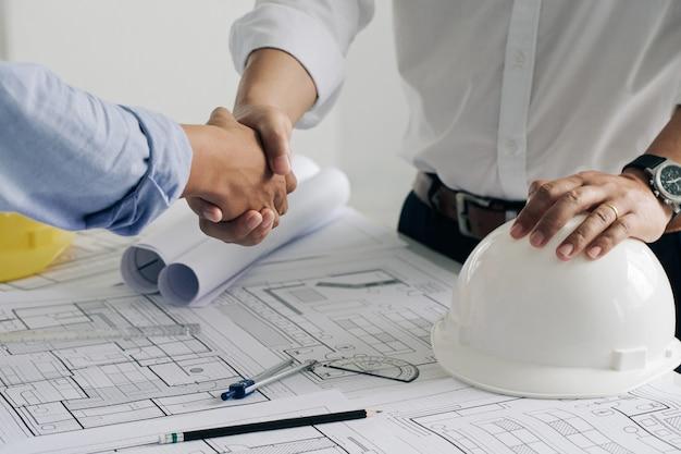 Handen schudden van samenwerking bouwtechniek of architect bespreken een blauwdruk