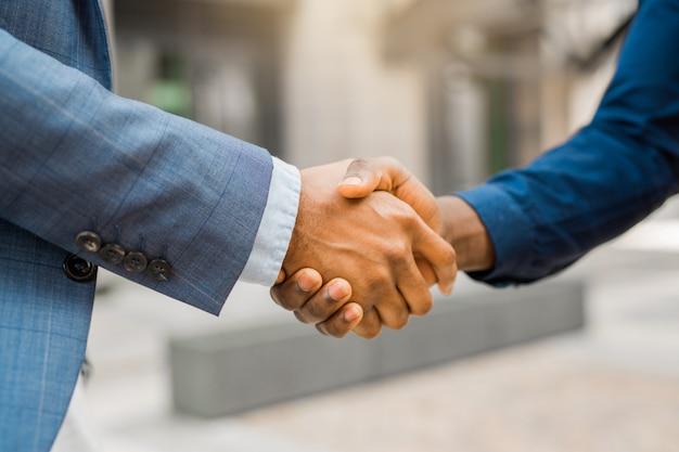 Handen schudden van twee jonge mannen in pakken