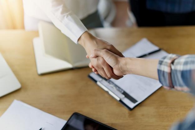 Handen schudden van twee zakelijke vrouwen over de tafel.