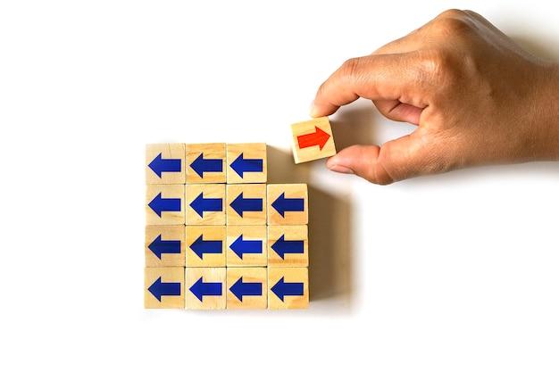 Handen selecteren houten kubussen met rode pijlen en aquarelpijlen in verschillende richtingen.