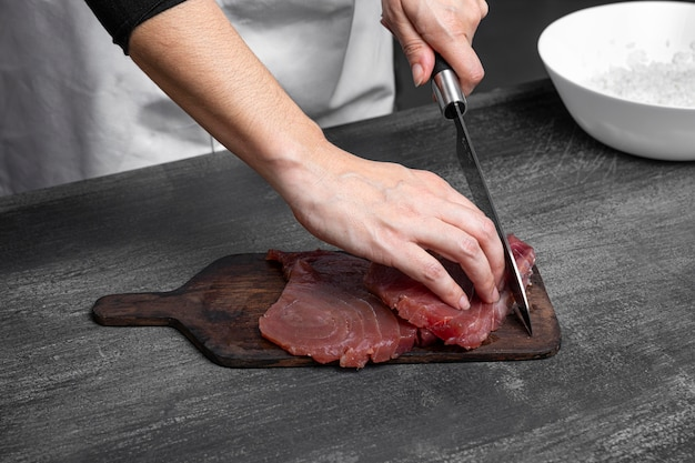 Handen snijden vis met mes hoge hoek