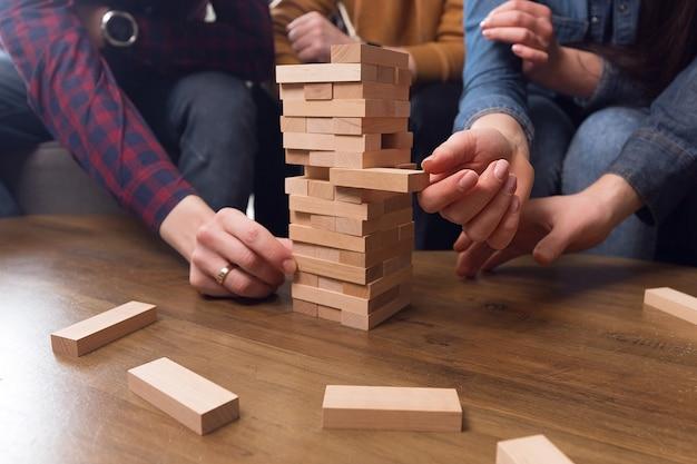 Handen staan een toren van houten stokken, teamwerkconcept, teamspel. hoge kwaliteit foto