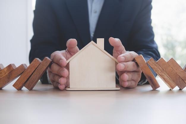 Handen stoppen het domino-effect voordat ze het huis vernietigen
