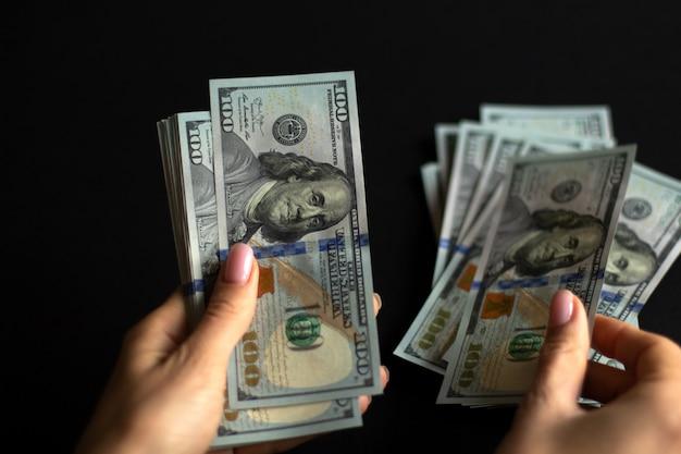 Handen tellen geldrekeningen in 100 dollar met zwarte achtergrond