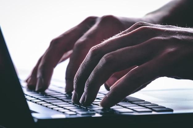 Handen typen op het toetsenbord van de computer. moderne stijl