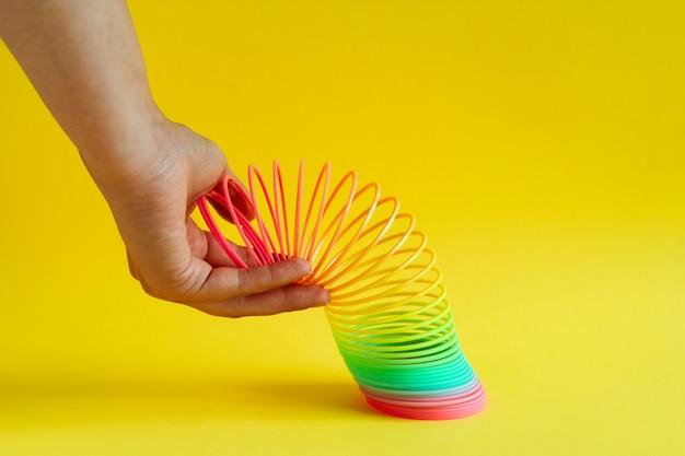 Handen uitgerekt plastic regenboog spiraal