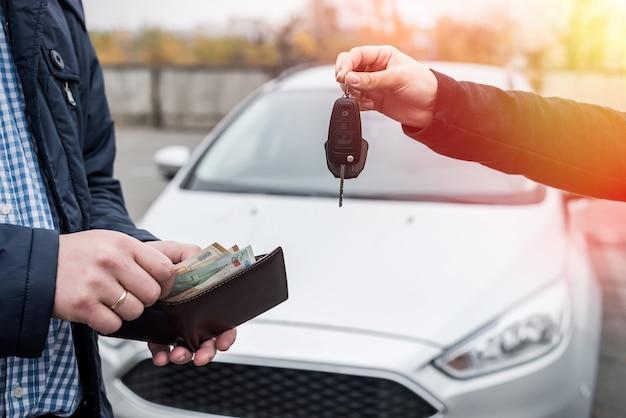 Handen uitwisselen met autosleutels en eurobankbiljetten