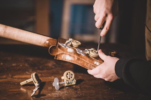 Handen van ambachtelijke gitaarbouwer schroeven, het bouwen van een contrabas