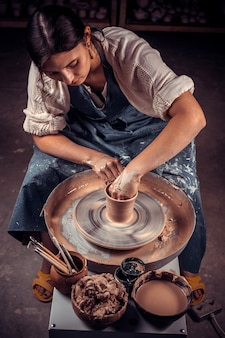 Handen van ambachten-kunstenaar maken van ambacht, aardewerk, beeldhouwer van verse natte klei op pottenbakkersschijf, modelleren van aardewerk op de pottenbakkersschijf