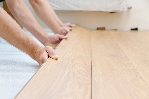 Handen van arbeiders die de rij planken in de vloerserie klemmen