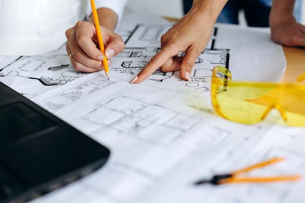 Handen van architecten werken aan blauwdrukken in het kantoor