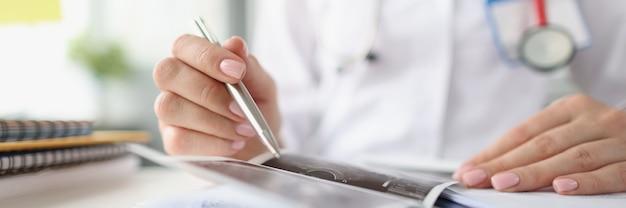 Handen van arts die echografie vasthoudt en onderzoekt