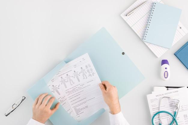 Handen van arts die medisch document in map met andere bestanden stopt terwijl hij op de werkplek zit met gereedschap, notitieboekjes en papieren