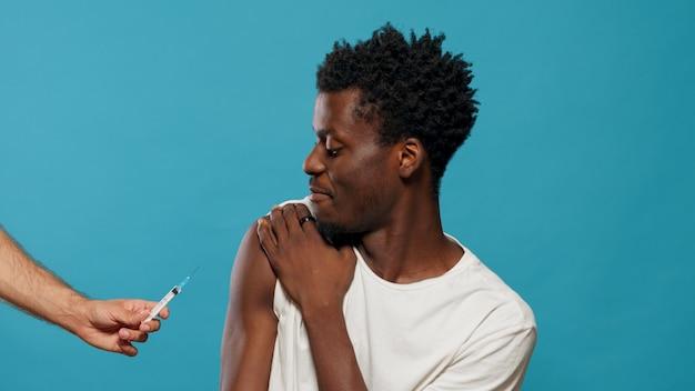 Handen van arts die zich voorbereidt om jongeman te vaccineren tegen coronavirus