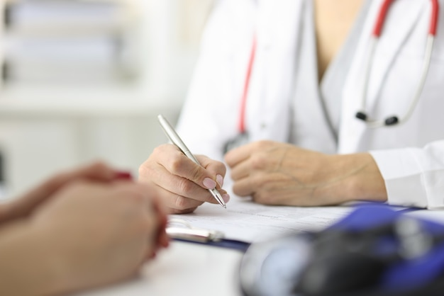 Handen van arts en patiënt op werktafel in medisch kantoor medisch onderzoek concept