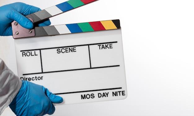 Handen van arts met film filmklapper, witte muur.