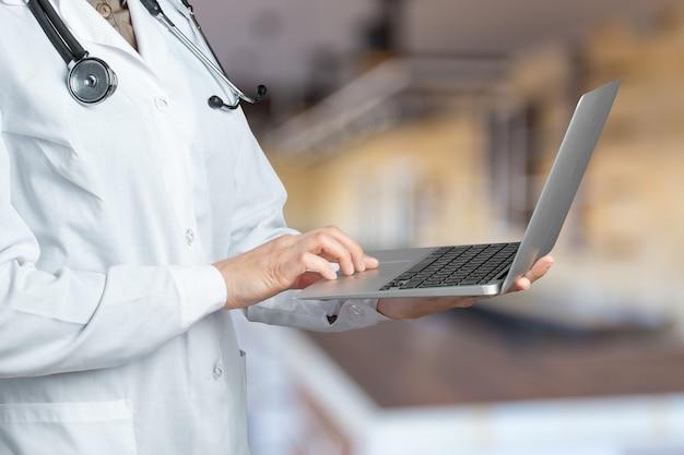 Handen van arts vrouw met laptop