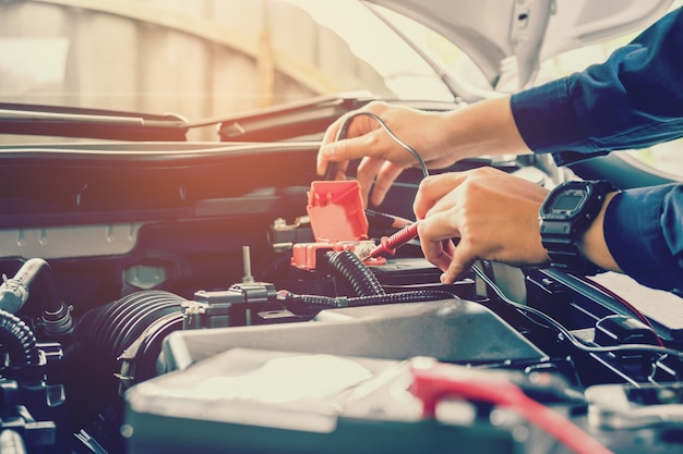 Handen van automonteur die in de autoreparatiedienst werken.