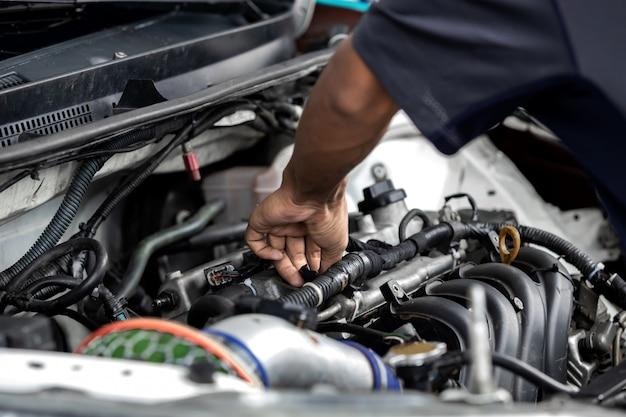 Handen van automonteur die motor van een auto in garage herstellen