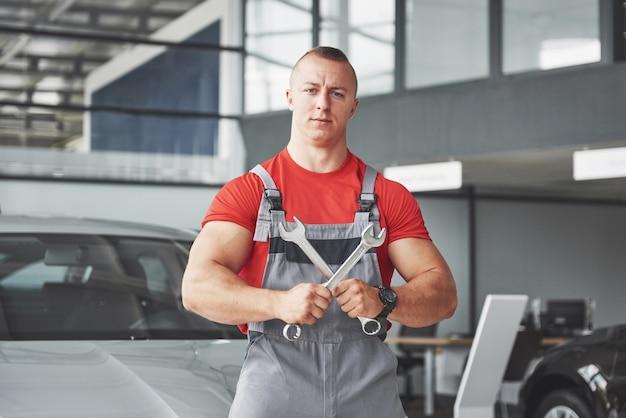 Handen van automonteur met moersleutel in garage.