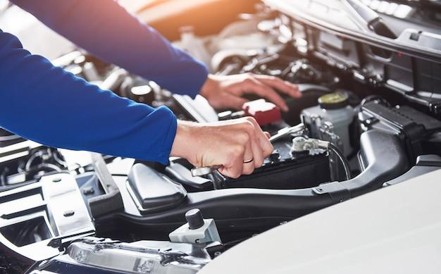 Handen van automonteur met moersleutel in garage
