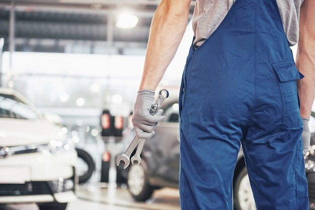 Handen van autowerktuigkundige met moersleutel in garage