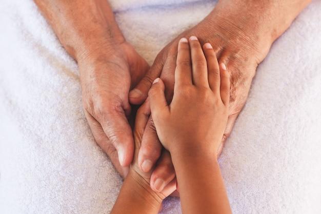 Handen van aziatisch kindmeisje die de bejaarde grootouder handen houden rimpelde huid met het voelen van zorg en liefde