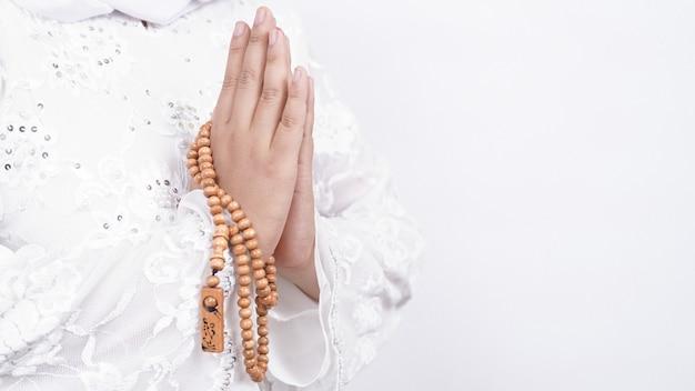 Handen van aziatische moslimvrouw die de gastvrije gasten van gebedparels dragen