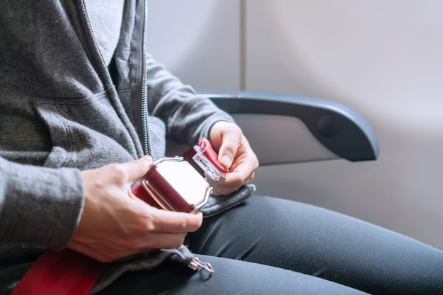 Handen van aziatische vrouw passagier veiligheidsgordel zittend op het vliegtuig. reis concept.