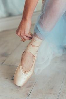 Handen van ballerina in blauwe tutu rok zet pointe-schoenen op been in witte lichte zaal