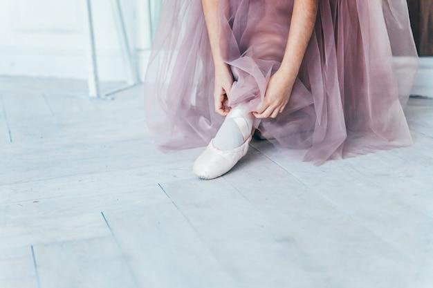 Handen van ballerina in tutu rok zet pointe-schoenen op been in witte lichte zaal