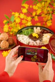 Handen van bebouwde vrouw die traditioneel voedsel op haar smartphonecamera fotograferen