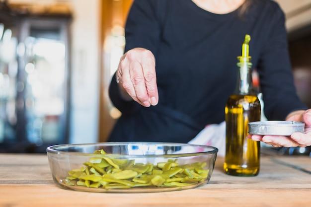 Handen van bejaarde vrouw koken in de keuken