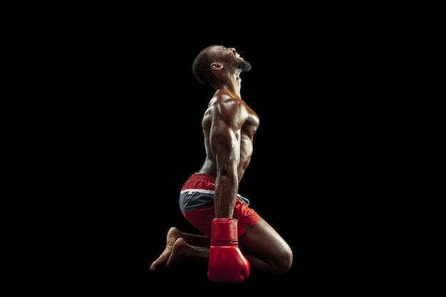 Handen van bokser op zwarte achtergrond. kracht, aanval en bewegingsconcept. fit afro-amerikaanse model in beweging. afro gespierde atleet in sportuniform. sportieve man tijdens het boksen