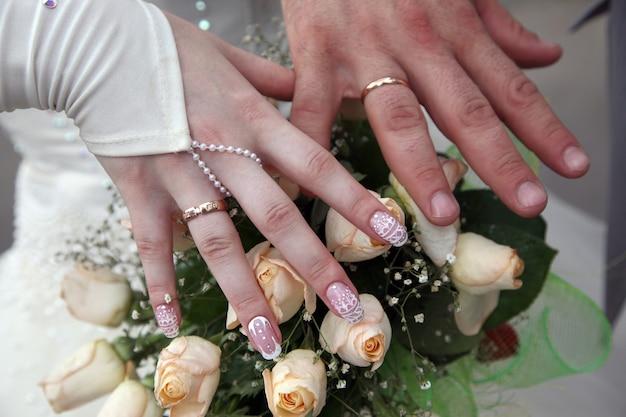 Handen van bruid en bruidegom bij huwelijksboeket