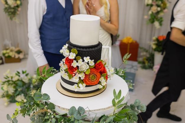 Handen van bruid en bruidegom knippen van een plakje bruidstaart.