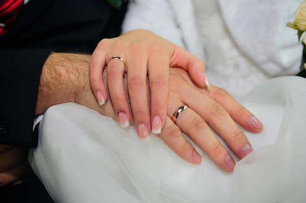 Handen van bruid en bruidegom met gouden trouwringen op witte jurk