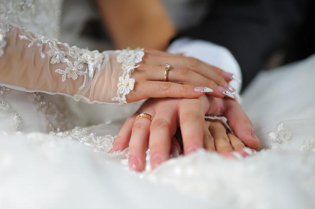 Handen van bruid en bruidegom met ringen op de jurk.