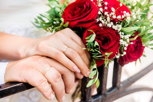 Handen van bruid en bruidegom met ringen op huwelijksboeket. huwelijk concept ...