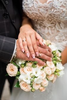 Handen van bruid en bruidegom met ringen op huwelijksboeket. huwelijk concept