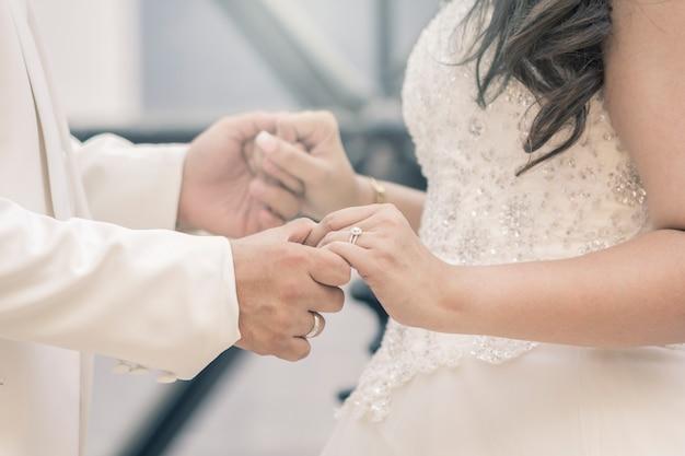 Handen van bruid en bruidegom met ringen