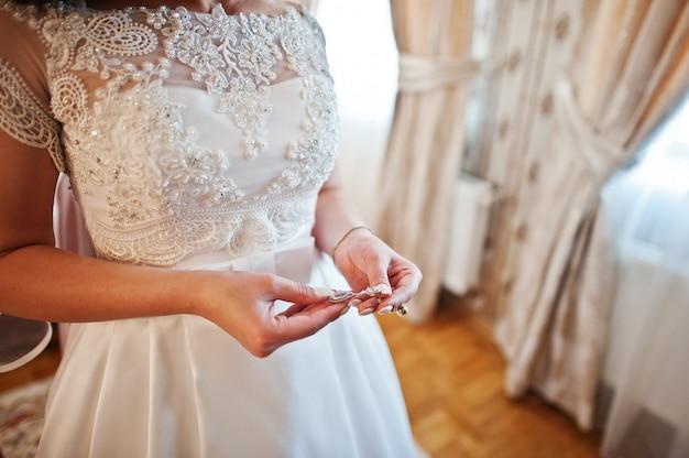 Handen van bruid met oorbellen op handen op trouwdag